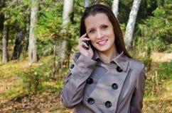 快乐的美丽的妇女,在木头的步行的 免版税库存照片