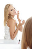 快乐的美丽的白肤金发的妇女,当应用一些面部crea时 库存照片