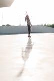 快乐的美国黑人的少年跳舞的后面看法在街道的 免版税库存图片