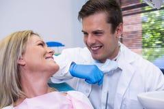 快乐的耐心看的牙医,当坐椅子时 免版税库存照片