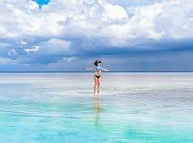 快乐的聪慧的深色的女孩在照片的水跳 一个天堂般的地方,美好的海景,在的云彩 免版税库存图片