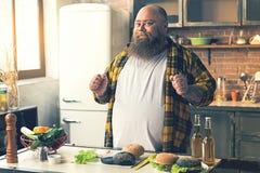 快乐的肥胖人喜欢烹调快餐 库存图片