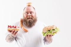 快乐的肥胖人更喜欢不健康吃 免版税库存照片