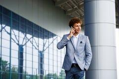 快乐的英俊的年轻红发商人画象谈话在电话 库存照片
