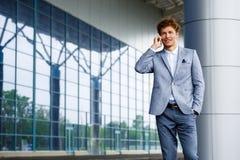 快乐的英俊的年轻红发商人画象谈话在电话 免版税库存照片