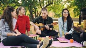 快乐的行家是唱歌,并且弹获得的吉他坐毯子在有朋友的公园和乐趣,人们是 股票视频