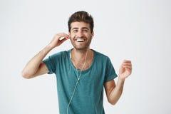 快乐的西班牙人演播室画象拿着耳机用手,听的音乐和跳舞与的蓝色T恤杉的 免版税图库摄影
