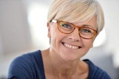 快乐的资深妇女佩带的镜片画象  免版税库存图片