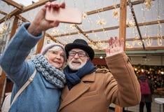快乐的资深拍在电话的丈夫和妻子照片 免版税库存图片