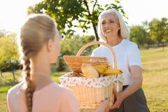 去快乐的资深的妇女有与她的孙女的一顿野餐 免版税库存图片