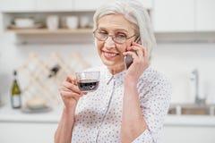 快乐的资深主妇谈话在电话在厨房里 免版税库存图片