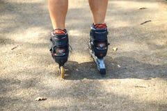 快乐的运动的人乘坐滑旱冰的50-55岁在秋天季节的公园,rollerblading作为所有的健康锻炼 免版税库存图片