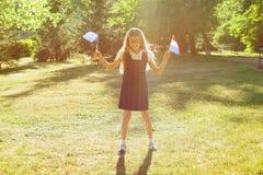 快乐的迷人的矮小的女小学生在手欧盟和荷兰上的拿着两面旗子 背景城市公园 库存照片