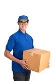 快乐的送货人 拿着纸板箱的愉快的年轻传讯者 免版税库存图片