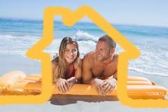 快乐的逗人喜爱的夫妇的综合图象在说谎在海滩的泳装的 图库摄影