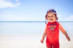 快乐的逗人喜爱的愉快的微笑的婴孩孩子太阳防护套服海滩蓝色海天空遮光剂背景拷贝空间 库存图片