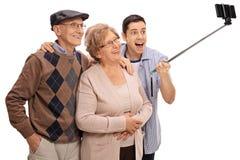 快乐的采取一selfie用棍子的前辈和一个年轻人 免版税库存照片