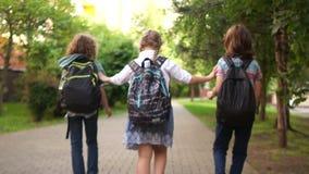 快乐的青少年从学校返回,笑并且催促,运载他们的背包,背面图 r 股票视频