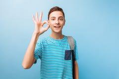 快乐的青少年的人调查照相机,显示OK标志 免版税库存照片