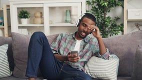 快乐的非裔美国人的人是唱歌和听到在放松在现代公寓的长沙发的耳机的音乐 股票录像