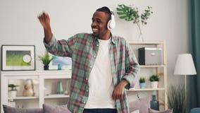 快乐的非裔美国人的学生跳舞唱歌并且听到音乐通过在家放松无线的耳机 股票录像