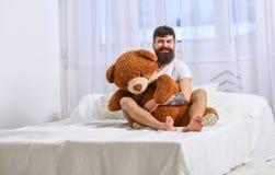 快乐的面孔的人拥抱巨型玩具熊 人坐床并且拥抱大玩具,在背景的白色帷幕 强壮男子与 免版税库存照片