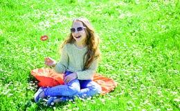 快乐的面孔的女孩花费休闲户外 Fashionista概念 摆在与太阳镜纸板微笑的嘴唇的孩子 库存图片