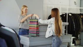 快乐的顾客使用智能手机支付被购买的衣裳,当站立在出纳员` s书桌时 售货员是 股票视频