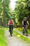 快乐的骑自行车的人夫妇在森林 图库摄影