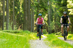 快乐的骑自行车的人夫妇在森林 库存照片