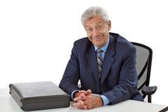 快乐的高级商人坐在服务台 免版税库存图片