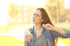 快乐的从一个巧妙的电话的妇女听的音乐 免版税库存照片