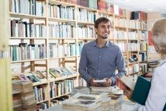 快乐的年轻人卖主帮助的顾客 免版税库存图片