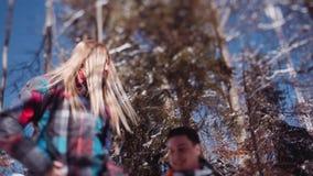 快乐的年轻人和可爱的时髦的妇女明亮的五颜六色的滑雪服装的 一件嬉戏的夫妇藏品的少量射击 影视素材