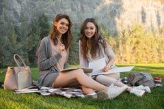 快乐的年轻人坐户外在公园文字笔记的两名妇女 图库摄影