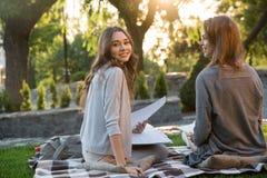 快乐的年轻人坐户外在公园文字笔记的两名妇女 免版税库存图片