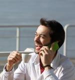 快乐的年轻人饮用的咖啡和谈话在手机 免版税库存图片