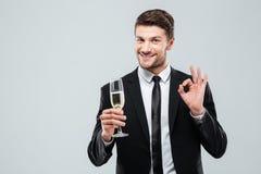 快乐的年轻商人饮用的香槟和显示好标志 图库摄影