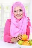 快乐的年轻回教妇女食用了果子早餐 免版税库存照片