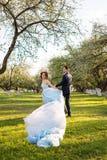快乐的年轻夫妇获得乐趣在开花的春天庭院 爱和浪漫题材 免版税图库摄影