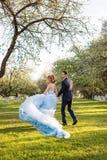快乐的年轻夫妇获得乐趣在开花的春天庭院 爱和浪漫题材 免版税库存图片