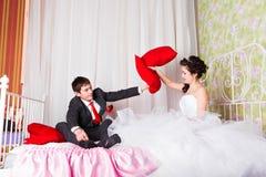 快乐的年轻婚礼夫妇把在家战斗在床上枕在 免版税库存图片