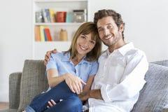 快乐的30岁的夫妇画象坐在现代公寓的沙发 图库摄影