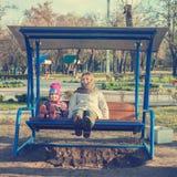 快乐的年轻母亲和小女儿在秋天停放 免版税库存图片
