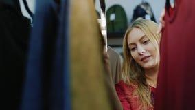 快乐的购物 一名年轻妇女的画象,看在一个挂衣架的衣裳在商店妇女` s衣物 股票视频