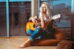 快乐的年轻白肤金发的女孩弹吉他 免版税库存照片