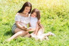 快乐的读的妇女教的女孩在草甸 库存图片