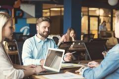 快乐的年轻的沟通男性和的妇女,当工作在办公室时 库存照片