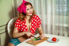 快乐的年轻美丽的妇女切了在的厨房的黄瓜 免版税库存照片
