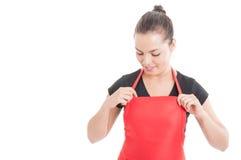 快乐的年轻超级市场女推销员佩带的围裙 图库摄影